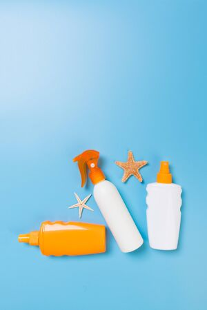 Sunscreen bottles with seashells on blue wooden table.