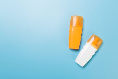 flat lay concept of summer travel vacation. Sunscreen bottle mock up on blue background top view with copy space.