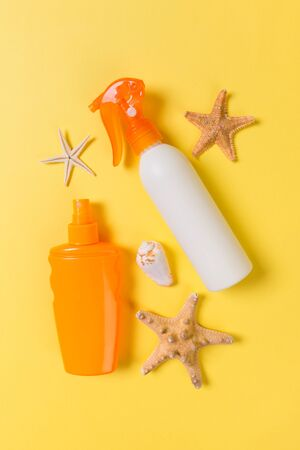sunscreen cream with starfish and seashells in bottles on yellow background, top view.