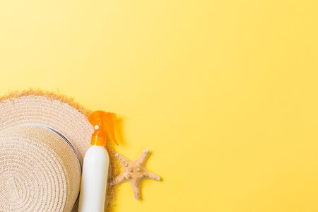 Sunscreen bottles with starfish and sunhat on yellow table with copy space. Travel healthcare accessories top view. Stock Photo