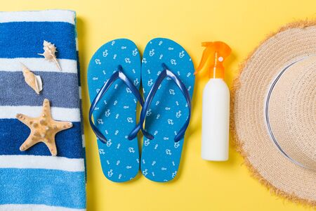 flip flops, straw hat, starfish, sunscreen bottle, body lotion spray on yellow background top view . flat lay summer beach sea accessories background, travel concept.