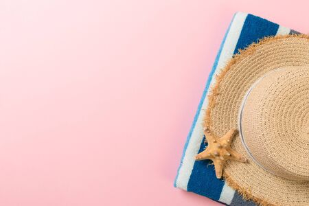 Straw hat, bluetowel and starfish On a pink background. top view summer holiday concept with copy space.