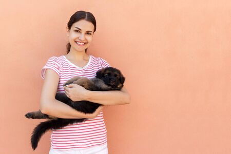 Happy young woman holding her pet puppy on orange background. Stock Photo