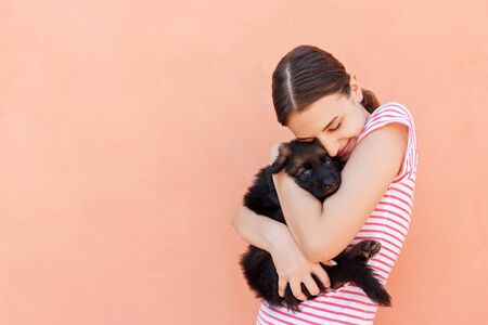 Beautiful girl hugging tight her cute small puppy.
