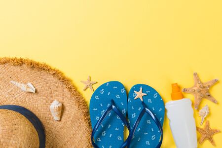 flip flops, straw hat, starfish, sunscreen bottle, body lotion spray on yellow background top view . flat lay summer beach sea accessories background, vacation concept. Stock Photo