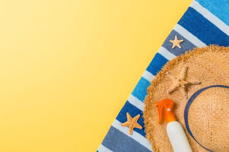 Beach flat lay accessories with copy space. Striped blue and white towel, seashells, staw sunhat and a bottle of sunblock on yellow background. Summer holiday concept. Stock Photo