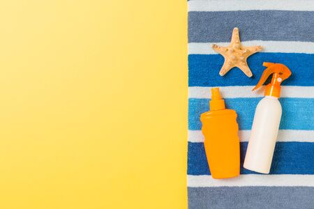 Beach flat lay accessories with copy space. Striped blue and white towel, seashells and a bottle of sunblock on yellow background. Summer holiday concept. Stock Photo