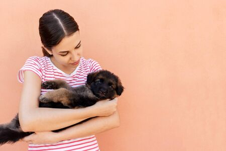 Beautiful woman in striped T-chirt holding small dog. Banco de Imagens