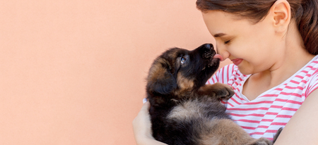 cute German shepherd puppy kissing woman's nose.