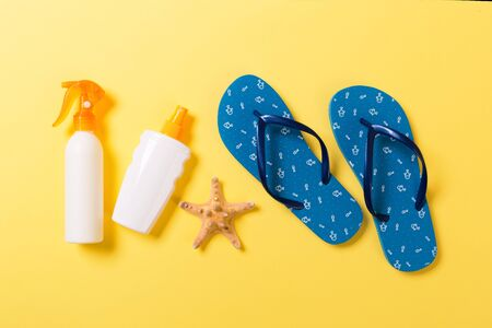 Sunscreen bottle or body spray on yellow background top view flat lay with copy space. Holiday vacation travel concept with beach sea accessories. Stock Photo