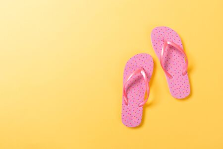 Pink flip flops on yelow Background. Top view with copy space.