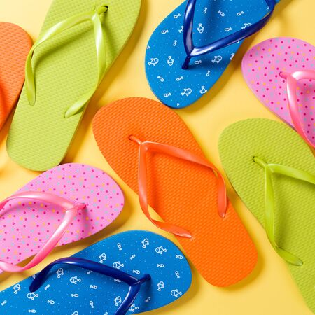 many colored flip flops on yellow background. Copy space top view. Stock Photo