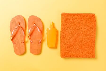 Orange flip flops with towel on yellow background top view flat lay with copy space. Holiday vacation travel concept with beach sea accessories. Stock Photo