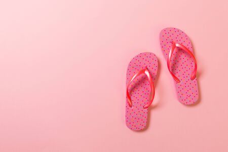 Coral flip flops on pink Background. Top view with copy space.