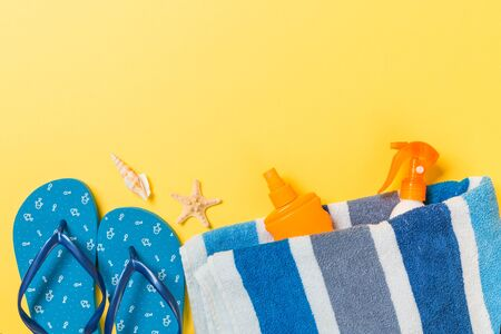 flip flops, straw hat, starfish, sunscreen bottle, body lotion spray on yellow background top view . flat lay summer beach sea accessories background, holiday concept. Stock Photo