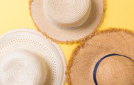 top view of straw beach hat on yellow background.