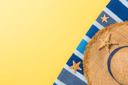 Straw hat, bluetowel and starfish On a yellow background. top view summer holiday concept with copy space. Stock Photo