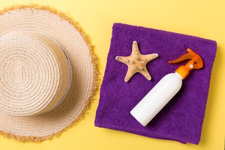 Beach flat lay accessories with copy space. Violet towel, seashells, staw sunhat and a bottle of sunblock on yellow background. Summer holiday concept.