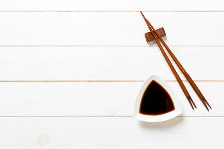 Soy sauce with chopsticks on white wooden table background. Banque d'images