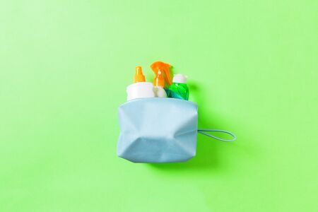 Top view of female cosmetics bag full of suncream spray, sunsreen, sunblock and body lotion and spf cream on green background with copy space. Directly above. Bright summer concept. Stockfoto
