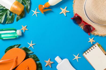 Beach accessories with straw hat, sunscreen bottle and seastar on blue background top view with copy space.