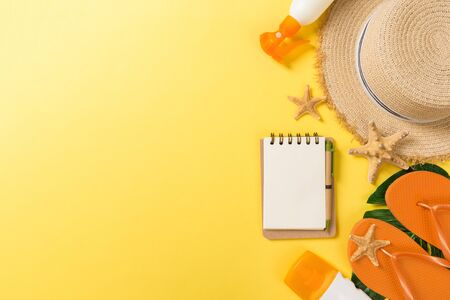 Beach accessories with straw hat, sunscreen bottle and seastar on yellow background top view with copy space. Фото со стока