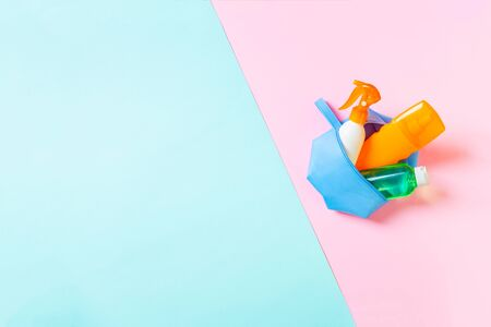 Top view of female cosmetics bag full of suncream spray, sunsreen, sunblock and body lotion and spf cream on blue and pink background with copy space. Directly above. Bright summer concept. Stockfoto