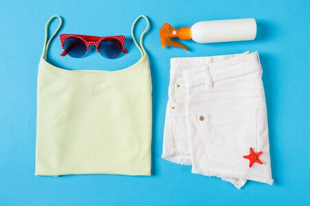 Flat lay composition with Beach accessories on blue color background. Summer holiday background. Vacation and travel items top view.