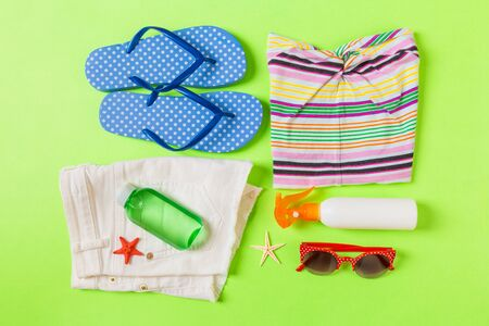 Flat lay composition with Beach accessories on green color background. Summer holiday background. Vacation and travel items top view. 版權商用圖片