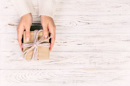 Woman hands give wrapped valentine or other holiday handmade present in paper with pink ribbon. Present box, decoration of gift on white wooden table, top view with copy space.