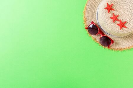 Beach hat with seashells on brown green table. summer background concept with copy space top view.