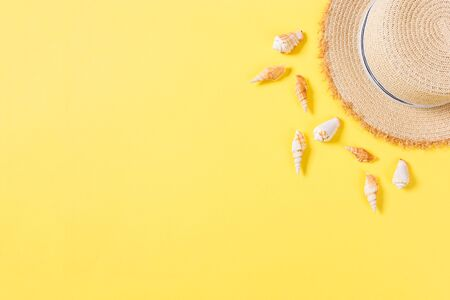 Beach hat with seashells on brown yellow table. summer background concept with copy space top view.