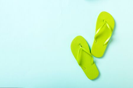green flip flops on blue background. Top view with copy space.