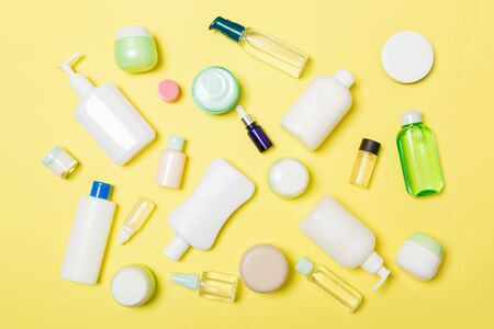 Group of plastic bodycare bottle Flat lay composition with cosmetic products on yellow background empty space for   design. Set of White Cosmetic containers, top view with copy space.