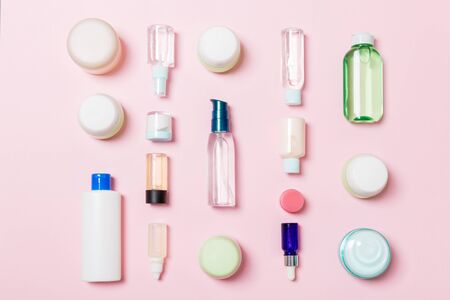 Group of plastic bodycare bottle Flat lay composition with cosmetic products on pink background empty space for   design. Set of White Cosmetic containers, top view with copy space.