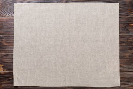 gray cloth napkin on rustic dark wooden background top view with copy space.