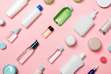 Top view of different cosmetic bottles and container for cosmetics on pink background. Flat lay composition with copy space. Stok Fotoğraf