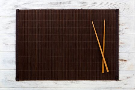 two sushi chopsticks with empty bamboo mat or wood plate on white wooden Background Top view with copy space. empty asian food background.