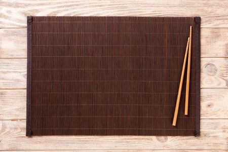 two sushi chopsticks with empty bamboo mat or wood plate on brown wooden Background Top view with copy space. empty asian food background.
