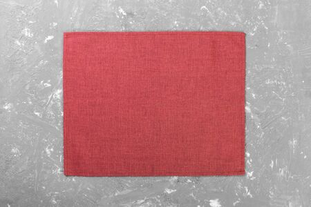 red cloth napkin on rustic cement background top view with copy space.