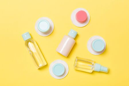Set of travel size cosmetic bottles on yellow background. Flat lay of cream jars. Top view of bodycare style concept.