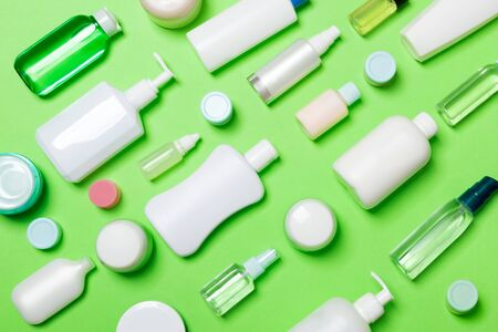Top view of different cosmetic bottles and container for cosmetics on green background. Flat lay composition with copy space.