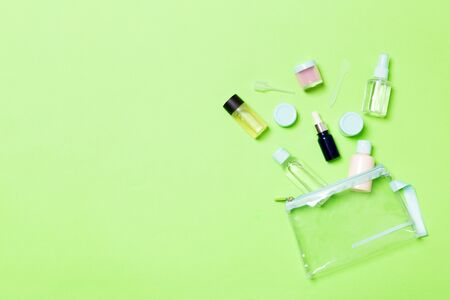 Group of small bottles for travelling on green background. Copy space for your ideas. Flat lay composition of cosmetic products. Top view of cream containers with cotton pads.