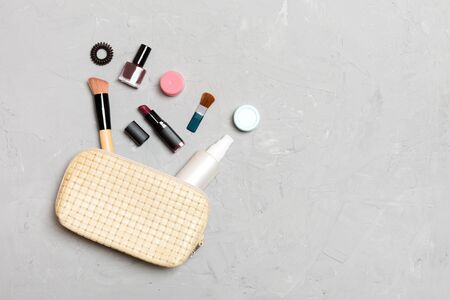 Top view of make up products fallen out of cosmetics bag on cement background. Cosmetic concept with space for your design.