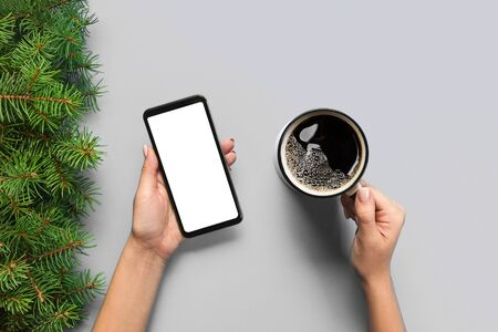 Female hands holding black mobile phone with blank white screen and mug of coffee. Mockup image with copy space. Top view on purple ackground, flat lay.