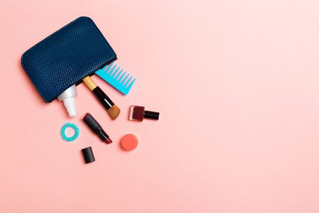 Make up products spilling out of cosmetics bag, on pink pastel background with empty space for your design. 免版税图像