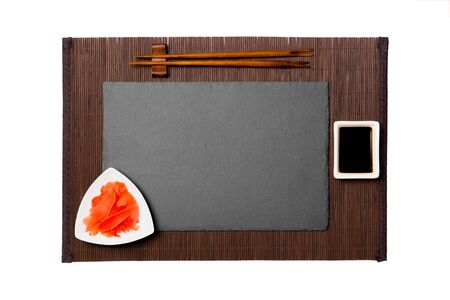 Empty rectangular black slate plate with chopsticks for sushi, ginger and soy sauce on dark bamboo mat background. Top view with copy space for you design.