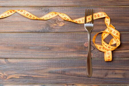 Top view of fork and curled measuring tape on wooden background. Diet concept with copy space.