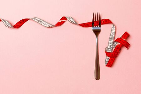 Fork surrounded with curled tape measure on pink background with copy space. Top view of proper diet concept.
