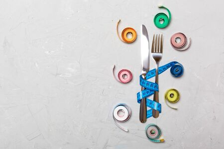 Composition of colored measuring tapes, fork and knife on cement background with empty space for your design. Overweight concept. Imagens
